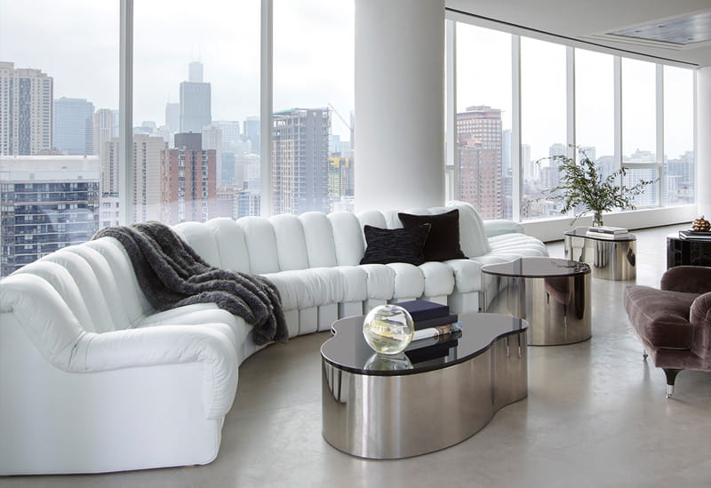 Grey furry throw on white sofa, room with a view.
